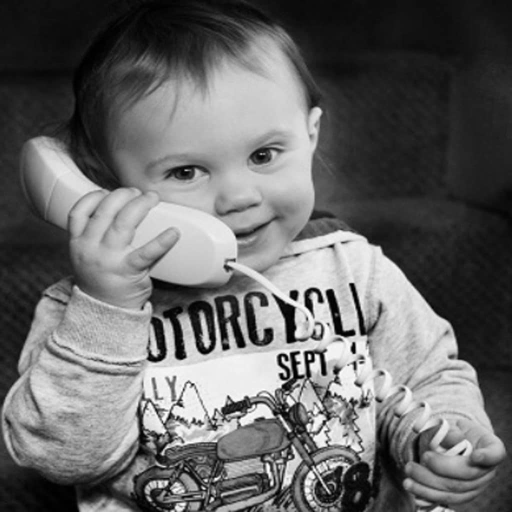 toddler putting phone on ear in black and white